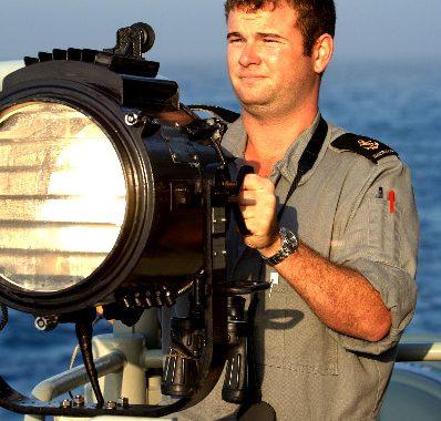 Leading Seaman Communications and Information Systems (LSCIS) Trent Nunn signals HMAS Westralia before a Replenishment at Sea (RAS)