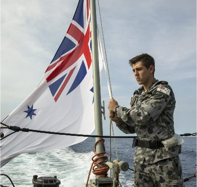 Seaman Communications and Information Systems Jarrod Callander lowers the Australian White Ensign as he participates in rehearsals for the Centenary of Anzac Day on-board HMAS Newcastle's Flight Deck as the ship and crew transit to the Middle East region in support of Operation MANITOU.