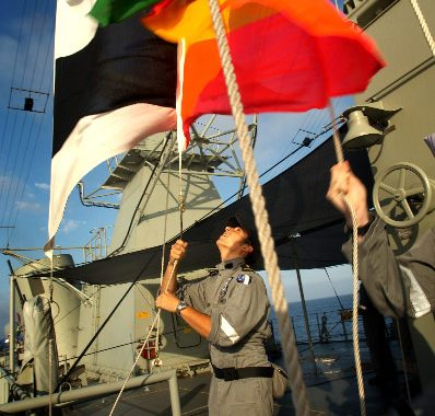 Able Seaman Communications and Information Systems (ABCIS) Ben Dazkiw hoists flags during a replenishment at sea (RAS) with HMAS Westralia