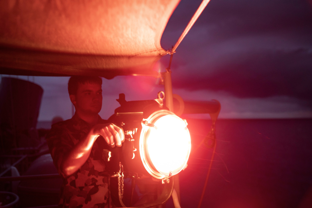 Able Seaman Communications and Information Systems Liam Hanly signals Royal Malaysian Navy ship KD Lekiu from HMAS Anzac during Indo-Pacific Endeavour 21.